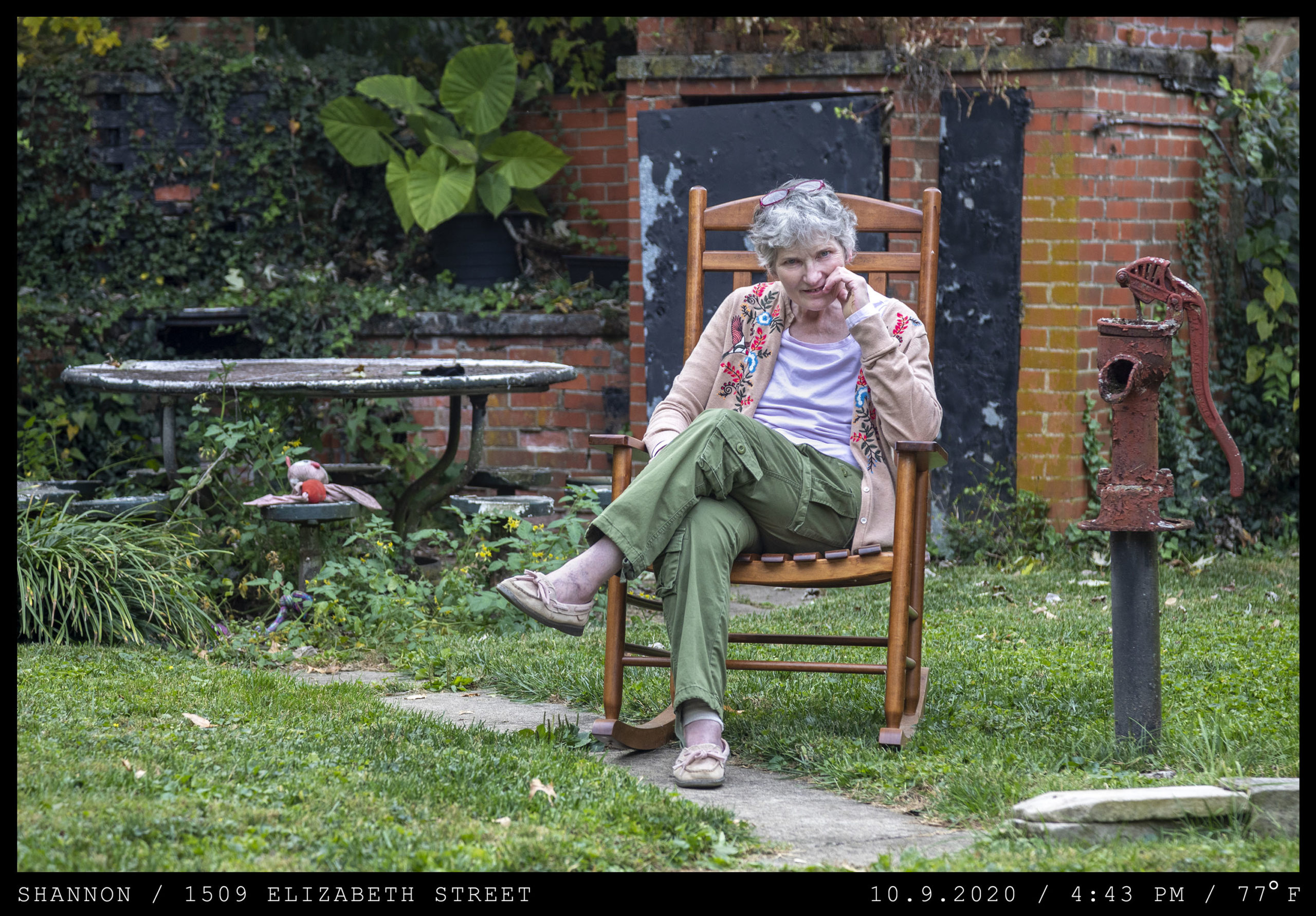 An older woman sits in a garden in a wooden rocking chair next to an antique water pump.