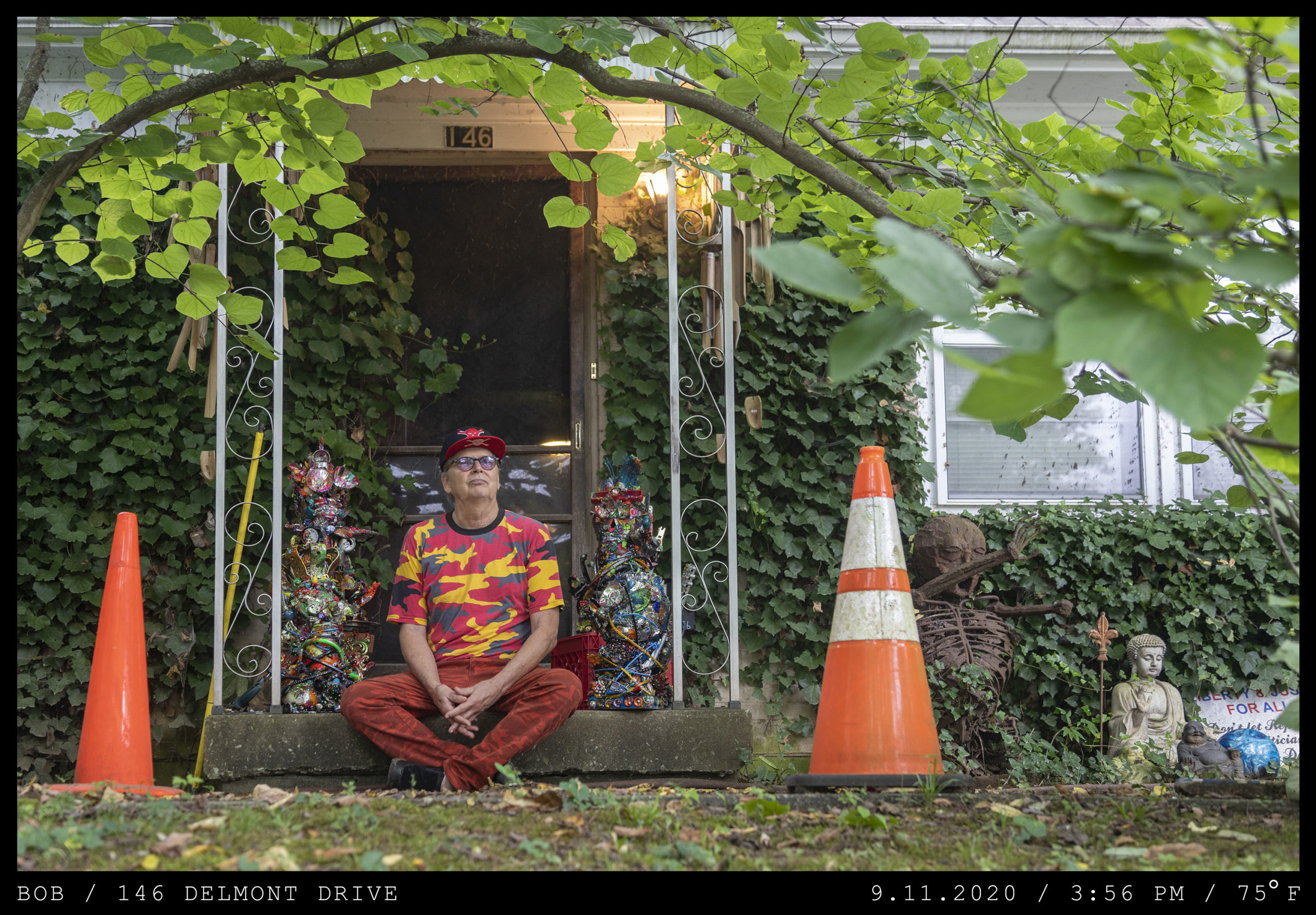 An older man dressed in a yellow, red, and black camo-patterned shirt and a red billed cap sits cross-ledded in a garden between two orange traffic cones.