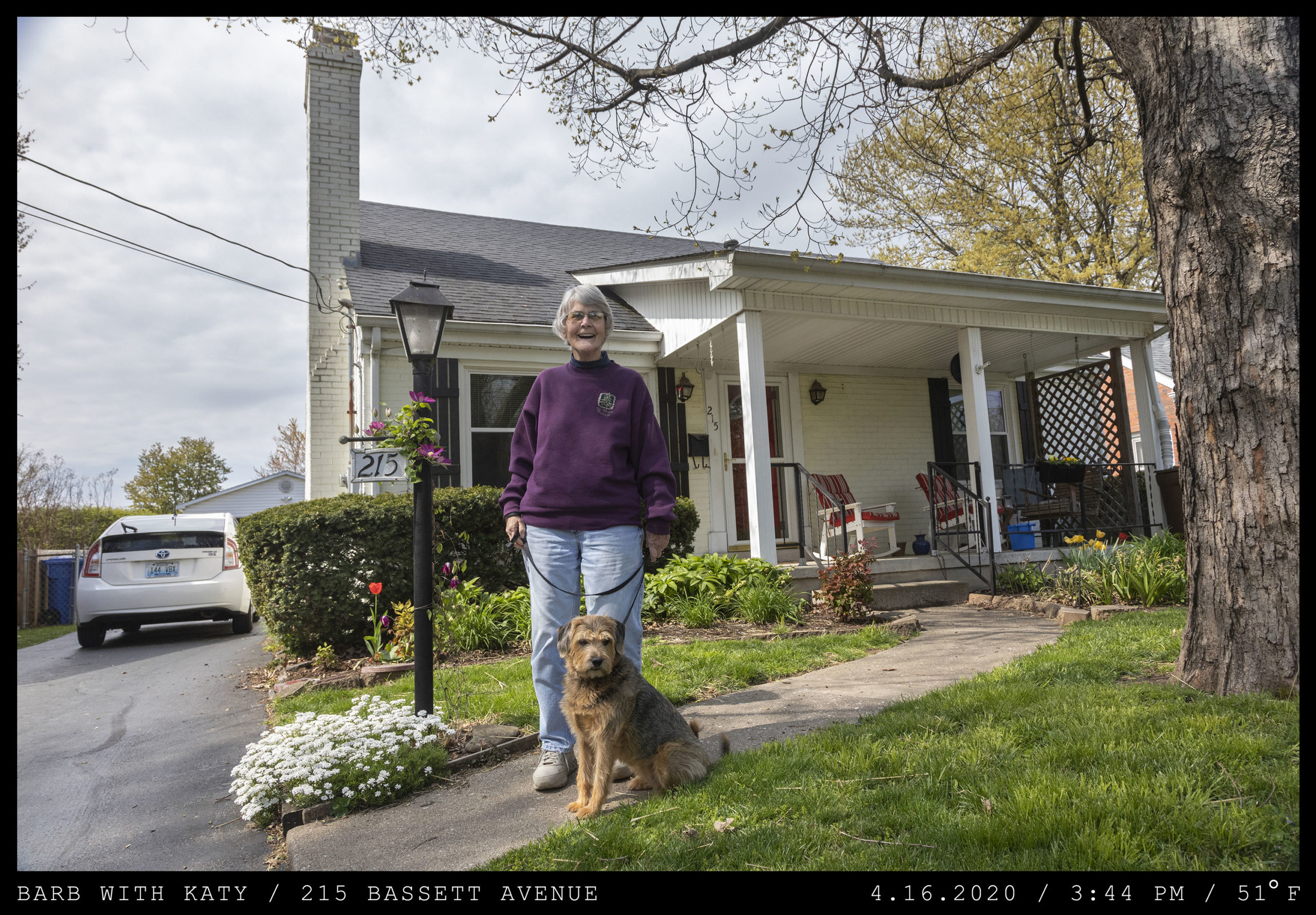 An smiling elderly woman holds an old dog on a leash next to the driveway of a white home with a front porch.
