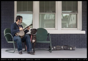 A man with dark hair and beard with grey highlights in denim is seated in a green metal garden chair on the porch of a dark blue brick home holding a banjo while a leashed dog stands to his side.