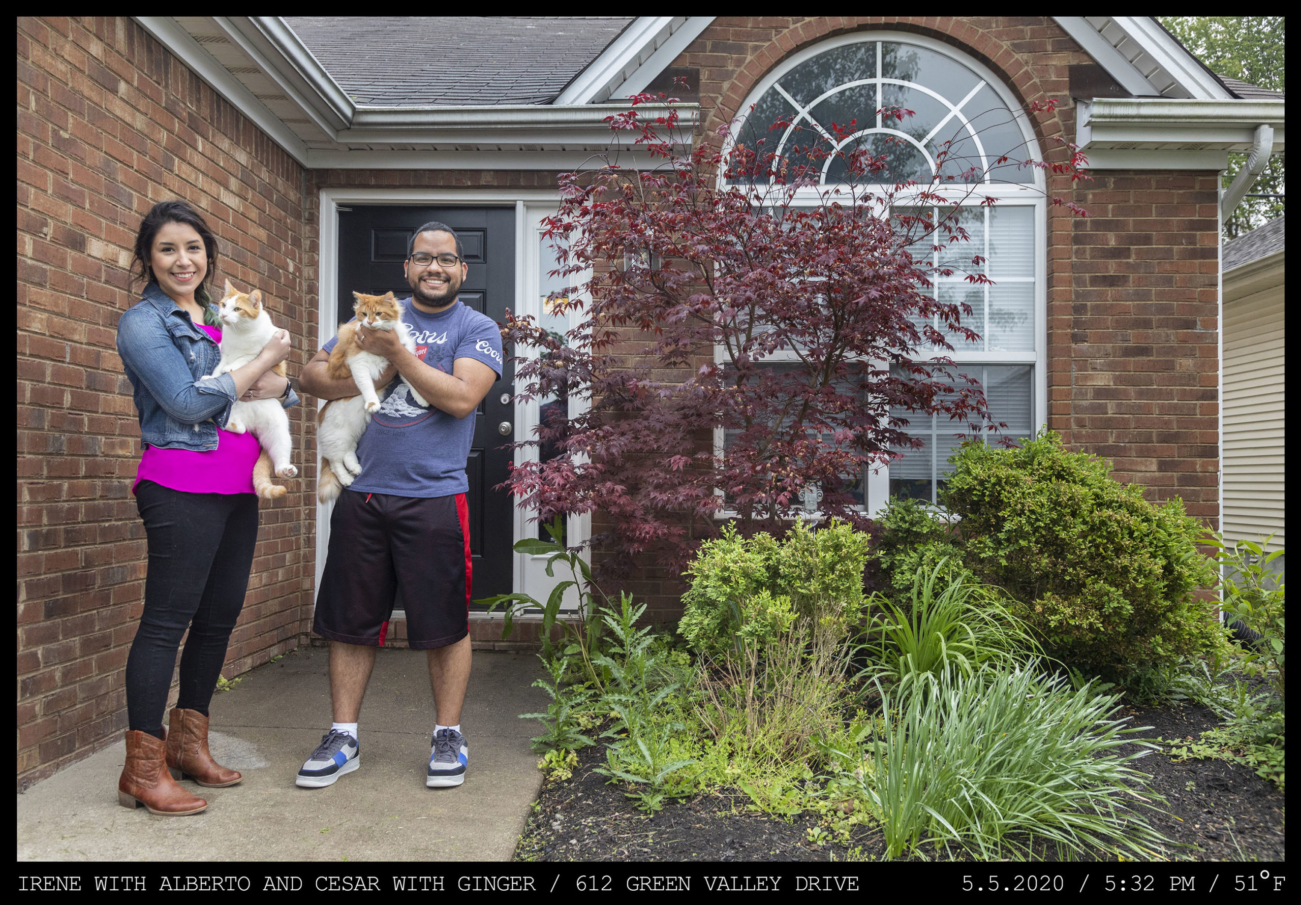 Two people hold cats: a woman with a neon pink shirt and a denim jacket stands next to a man in a Coors tee shirt at the front entryway of a brick home with a white framed arched window.